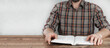 Opened Bible book in the hands of a man. Sitting at a wooden table