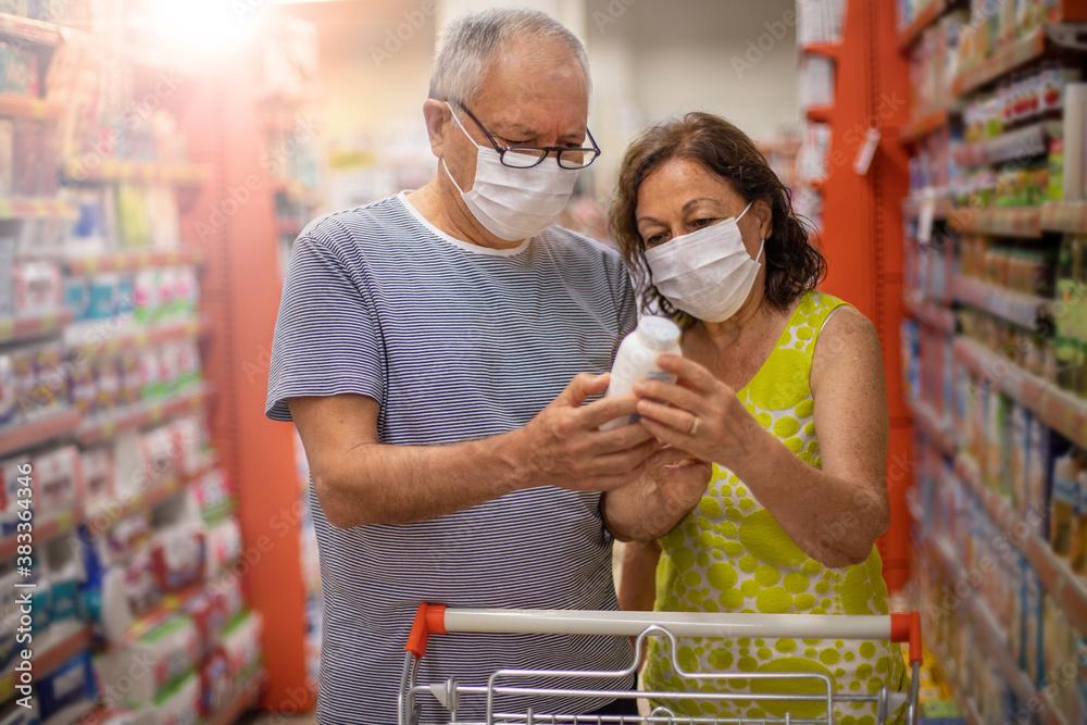 Fototapeta A senior couple shopping at the market with protective masks