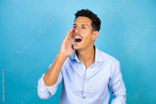 Fotografija Young handsome man wearing blue shirt over isolated blue background shouting and screaming loud to side with hand on mouth
