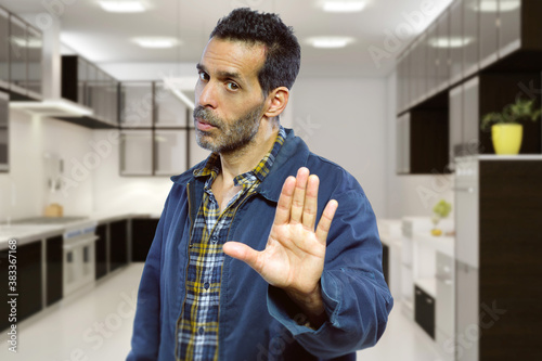 Fotografie, Obraz Small business owner with a restaurant or kitchen looking worried of covid shutdown and holding hands up as a stop gesture in response to rules and policies or customers