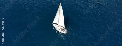 Aerial drone ultra wide photo of sailboat cruising deep blue sea