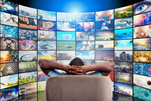 Man Has Fun Watching A Film And Relaxing On A Armchair. Concept Of Entertainment And Streaming Tv.