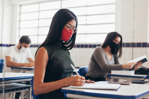 Brazilian college students wearing face masks sitting at the desk in the classroom Poster Mural XXL