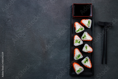 Fototapeta Japanese food, sushi restaurant. Salmon maki sushi rolls on black plate, flat lay. Seafood background obraz