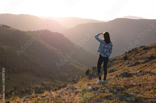 Young woman admiring sunset on the background of mountains Canvas Print