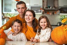 Happy Family! Mother And Her Three Children Sitting At Table With Pumpkins