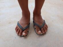Boy's Feet On Flip Flops Standing On The Concrete Floor