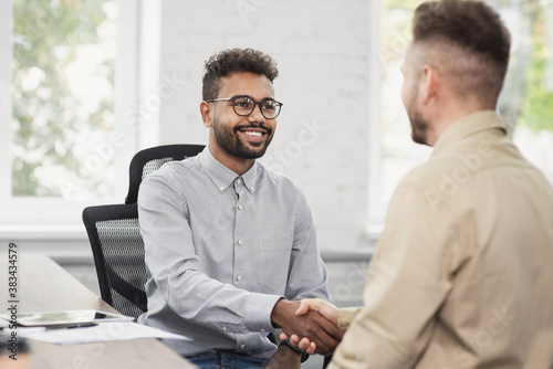 Foto Young men wearing smart casual clothes shaking hands while working