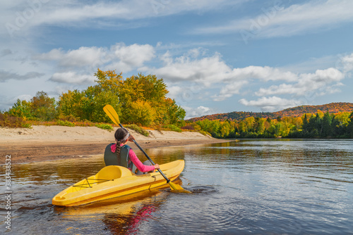 Obraz Kayak fun water sports down on river in Laurentians, Quebec. Canada travel destination. Woman kayaker kayaking in Mont-Tremblant during autumn. - fototapety do salonu