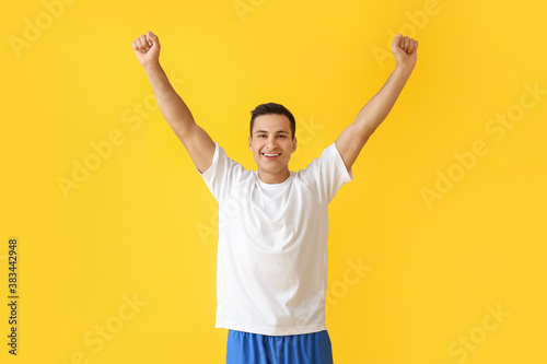 Sporty young man on color background. Concept of goal achievement Canvas Print