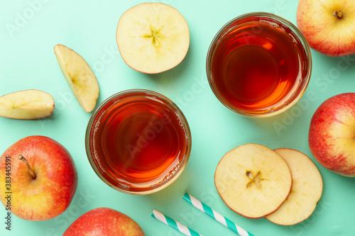 Fotografie, Obraz Apple slices, straws and glasses of apple juice on mint background