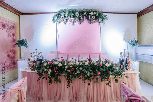 Fototapeta Festive table, arch, stands decorated with composition of pink flowers and greenery, candles in the banquet hall