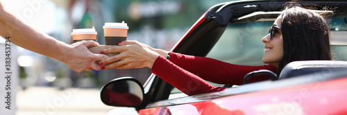Courier hands over coffee to woman in car Canvas Print