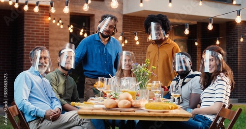 Fotografija Portrait of mixed-races people in face shields at dinner table in back yard and smiling to camera
