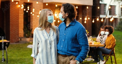 Fotografía Portrait of Caucasian middle-aged couple in medical masks hugging in yard at picnic