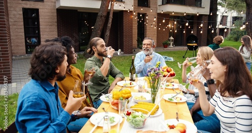 Happy multi ethnic family sitting at table with meal outdoor at picnic and toasting with juice and wine. Joyful young and old people having dinner and toast at party barbrque. Celebration on weekend.