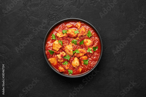 Fotografiet Chicken Madras Curry in black bowl on dark slate table top
