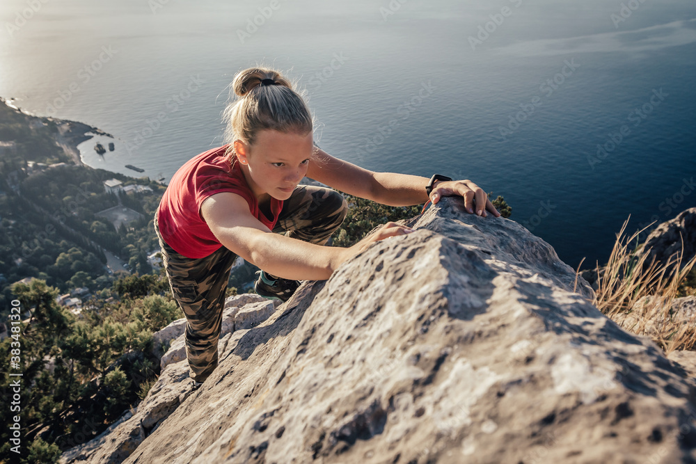Fototapeta Young strong girl climbs to top of cliff. Overcoming obstacles and courage. Ambitious climber climbing high mountain to achieve success