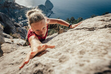 Brave Young Woman Climber Fearlessly Climbs Up Sheer Stone Wall In Mountains, Overcoming Obstacles. Dangerous Chasm Balancing, Adrenaline And Courage In Extreme Sports