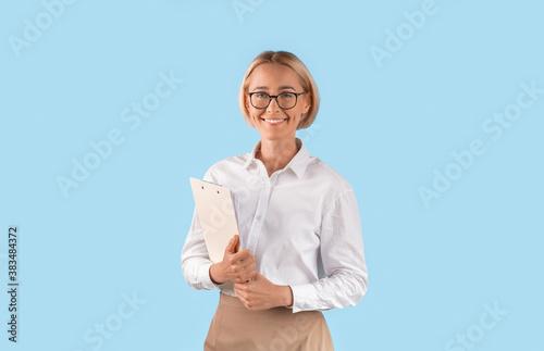 Fototapeta Portrait of happy businesswoman in formal wear and eyeglasses holding clipboard over blue studio background obraz