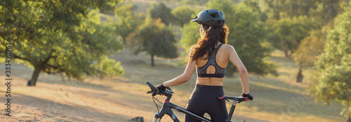 Young female cyclist cycling on rural road, side view. Canvas