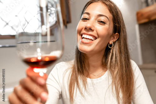Young caucasian beautiful woman toasting with red wine in her kitchen looking to Wallpaper Mural