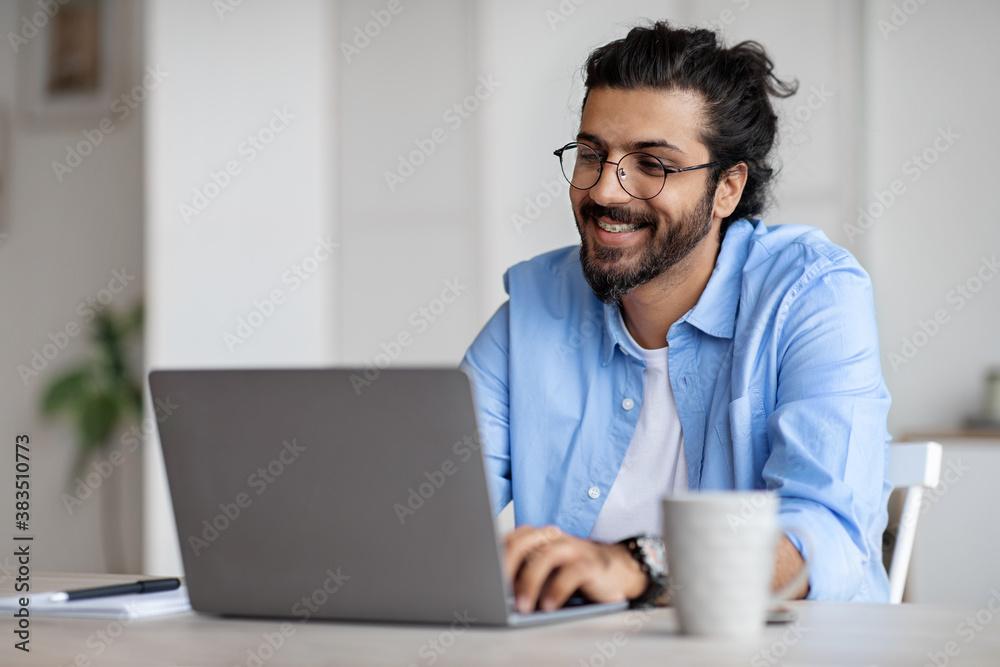Fototapeta Smiling Indian Writer Using Laptop Computer, Sitting At Desk In Home Office