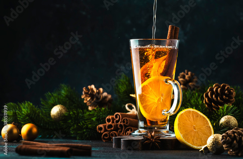 Obraz na plátně Christmas or New Year hot winter drink, spicy grog cocktail, punch or mulled wine with tea, lemon, rum, cinnamon, anise