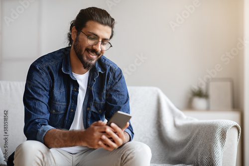 Obraz na plátně Handsome young indian guy sitting with smartphone at home, messaging with friend
