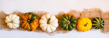 A Row Of Multicolored Small Pumpkins On Burlap On A White Wooden Background. Banner.