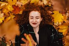 Happy Redhead Woman Lying On F...