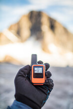 Mountaineer Holding Mini GPS Unit With Weather Forecast Showing.