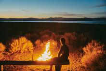 Young Man Sitting Near Campfire Near Mono Lake At Night In California.