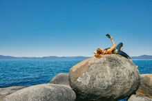 Young Woman Laying By Lake Tahoe Reading A Kindle Book During The Day