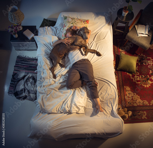 Tablou Canvas Portrait of a woman, female breeder sleeping in the bed with her dog at home