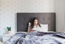 Young Girl Sitting In Bed At H...