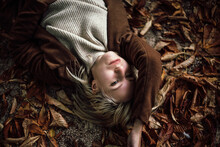 Portrait Of Blond Woman Lying On Autumn Leaves