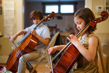 Brother And Sister Practicing Cello Together In Living Room