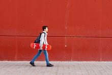 Side View Of Teenage Boy Walking On Sidewalk With Skateboard