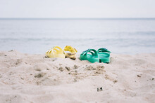 Two Pairs Of Sandals On A Sandy Beach In Summer