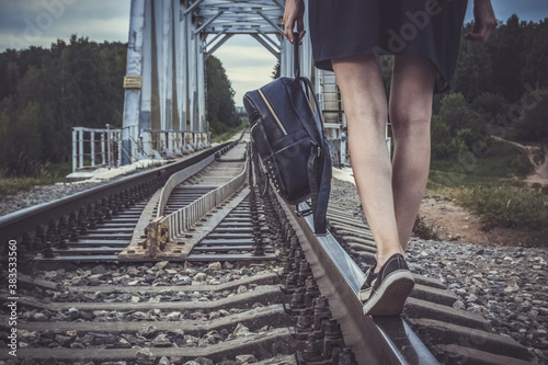 Foto A girl with a backpack walks on a railway across a bridge: a dramatic background