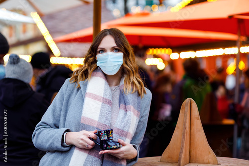 Fotomural Woman with medical mask drinking hot punch, mulled wine on German Christmas market