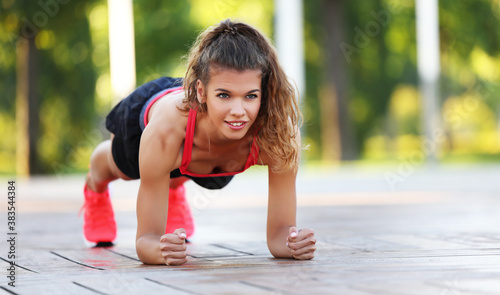 Obraz Active fit woman doing plank exercise in park. - fototapety do salonu