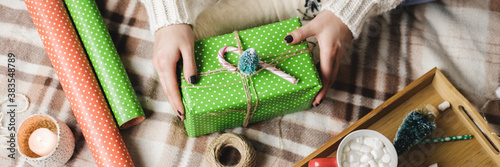 Photo Young woman sits on plaid in cozy knitted woolen white sweater, socks and wraps Christmas gift in polka dot wrapping paper