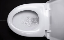The White Flush Toilet Bowl That The Water Is Draining. Concept Of Flushing Away Something.
