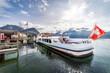 Lugano, Tessin, Schweiz. Ein Kursschiff an der Schiffsanlegestelle. Schweizer Flagge, Tourismus, Urlaub, Reisen.
