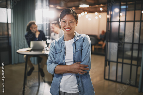 Asian businesswoman smiling with colleagues sitting in the backg