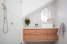 Brushed Brass Tap Mixer On Timber Vanity With White Basin Bowl Against White Tiled Wall In A New Modern Elegant Bathroom Lit By Natural Light From A Nearby Window Modern Interior House Renovation New