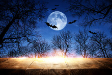 Halloween Holiday Concept. Empty Rustic Table In Front Of Scary And Misty Night Sky, Forest And Full Moon Background. Ready For Product Display Montage