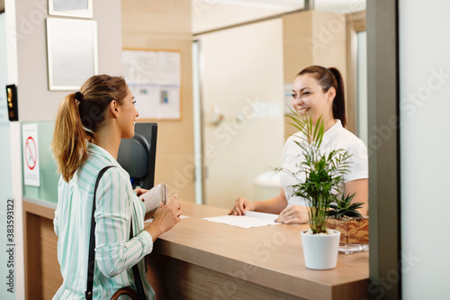 Happy woman talking to a receptionist while arriving at the spa. Fotobehang